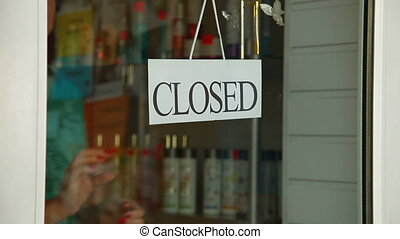 We Are Open - Business owner turns sign from closed to open...