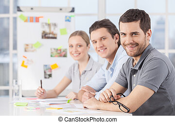 We are strong when we are together. Three cheerful young colleagues sitting together at their working place and smiling at camera