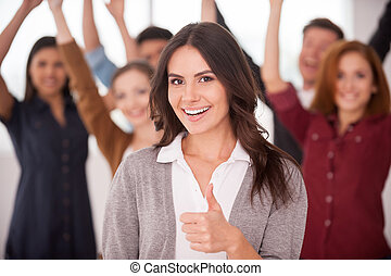 We are successful team! Beautiful young woman showing her thumb up and smiling while group of happy young people standing on background and keeping arms