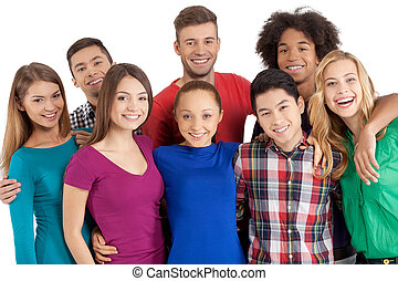 We are team! Group of cheerful young multi-ethnic people standing close to each other and smiling at camera while standing isolated on white