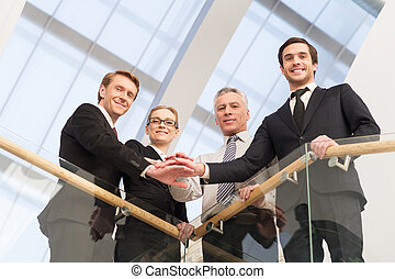 We are the best. Low angle view of four confident business people standing close to each other and holding hands together
