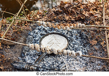 We bake bread from the dough in a pan on the coals of the fire