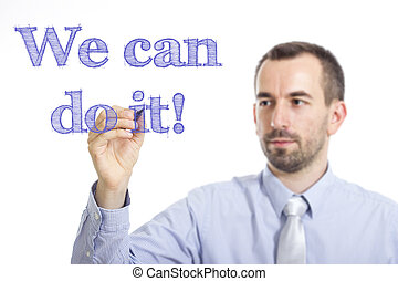 We can do it! - Young businessman writing blue text on transparent surface