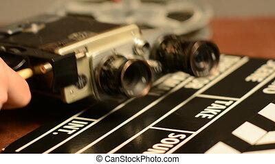 We change the lens on a retro film camera. Movie clapper lie...