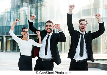 We did it! Three exited young business people keeping arms raised and expressing positivity while standing outdoors with office building in the background
