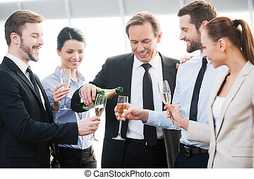 We got a contract! Group of happy business people holding flutes with champagne and smiling while standing close to each other indoors