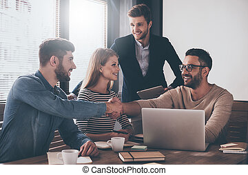 We have a deal! Two men shaking hands and looking at each other with smile while sitting at the business meeting with their coworkers