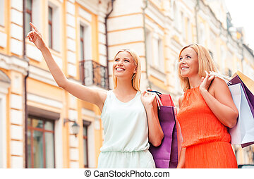 We have to visit this shop. Low angle view of cheerful young woman and her mother carrying shopping bags and looking away while walking outdoors