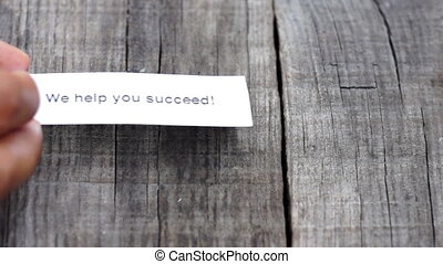 We help you succeed paper sign on wood background.