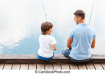 We love fishing together. Rear view of father and son ...