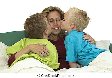 We Love Mommy - Mother and two sons lying happy in bed,...