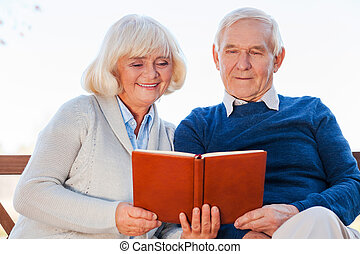 We love reading together. Cheerful senior couple reading a book together while sitting on the park bench