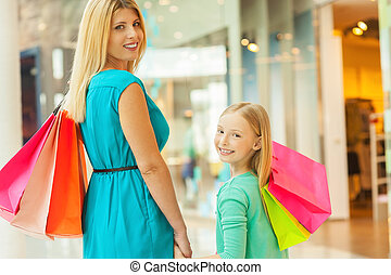 We love shopping together! Cheerful blond hair mother and...