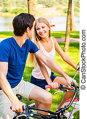 We love spending time together! Beautiful young smiling couple riding their bicycles in park together and looking at each other