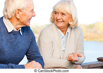 We love spending time together. Happy senior couple talking to each other and smiling while standing outdoors