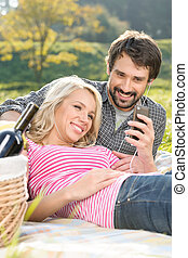 We love this song. Loving young couple listening to the music on picnic together