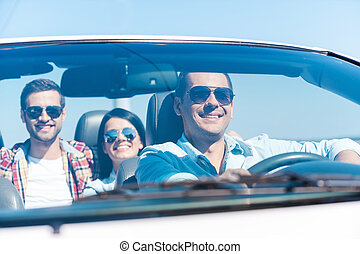 We love traveling together! Group of young happy people enjoying road trip in their white convertible