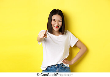 We need you. Confident asian woman smiling, pointing finger at camera, inviting to join her, beckon or choosing someone, standing over yellow background