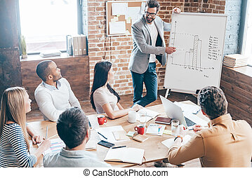 We should use this strategy! Top view of handsome young man in glasses standing near whiteboard and pointing on the chart while his coworkers listening and sitting at the table in office