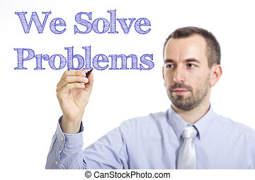We Solve Problems - Young businessman writing blue text on transparent surface