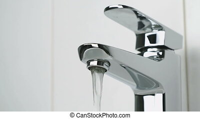 Weak flow of water pouring from chrome faucet