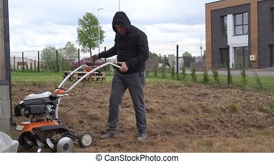 Weak man start engine of cultivator and work hardly in townhouse yard