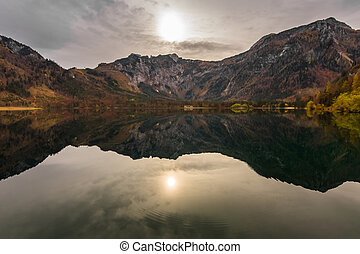 weak sun in a colorful autumn landscape on a mountain lake while hiking