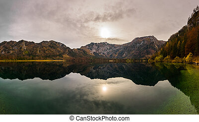 weak sun in a colorful mountain landscape on a lake panorama