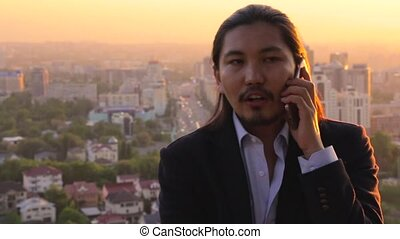 Wealthy businessman talking on a cellphone with a beautiful city in the background