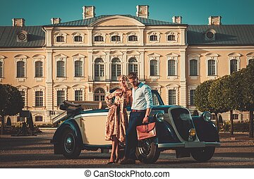 Wealthy couple near classic convertible against royal palace...