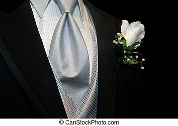 Rose pinned to black tuxedo with silver tie.