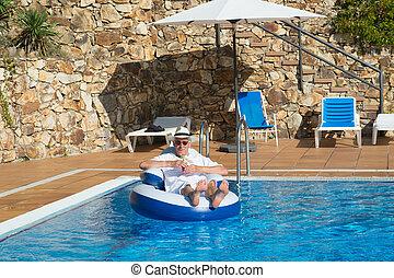 wealthy man relaxing in own swimming pool