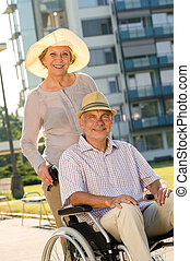 Wealthy senior man in wheelchair with wife