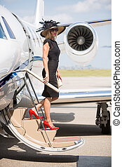Wealthy Woman Disembarking Private Jet At Airport Terminal -...