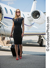 Wealthy Woman With Luggage Walking Against Private Jet