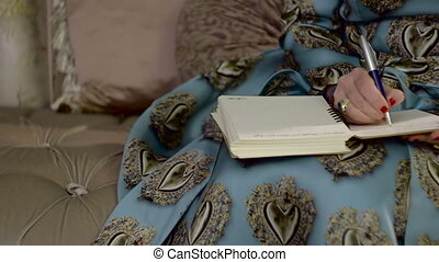 Wealthy Woman Writes In Notebook. Element of Luxury
