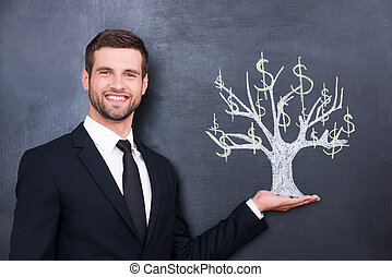 Wealthy world. Handsome young man smiling and looking at camera while standing against chalk drawing on the blackboard