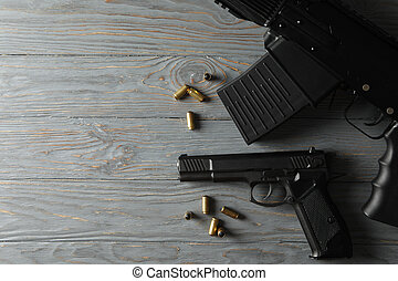 Weapon on gray wooden background, top view