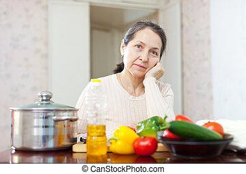 weariness mature woman at kitchen