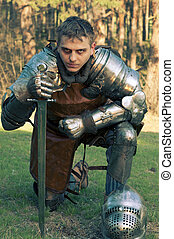 Weary knight stands on a glade - Knight holding sword in a...