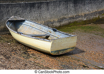 Weather-beaten white and blue dinghy with peeling paint, out of water on a concrete slipway