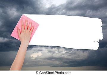 hand deletes dark rain clouds on sky by pink rag