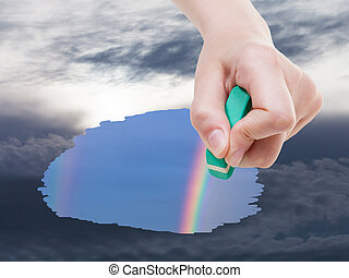 weather concept - hand deletes storm clouds on sky by rubber eraser from image and rainbow are appearing