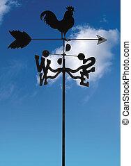weather vane - black iron weather vane against blue sky with...