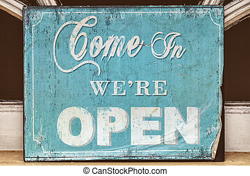 Weathered come in we're open sign