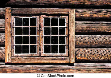 Weathered log house wall window
