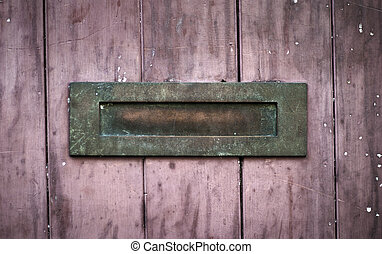 Weathered rusty letter box on red wood - An old weathered...