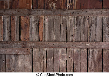 weathered wood of old barn wall with gaps between planks,...