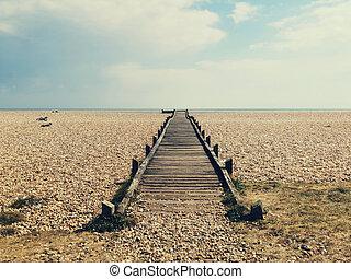 Weathered wooden board walk or path leading across shingle beach to the sea