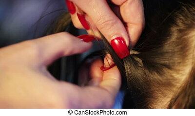 Weaving braids brunette - Hairdresser braids braid girl with...